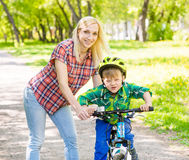 Happy mother with her son having fun, riding a bicycle Stock Photography