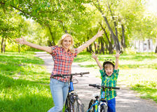 Happy mother with her son having fun, riding a bicycle Stock Images