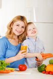 Happy mother with her son in the kitchen Stock Photos