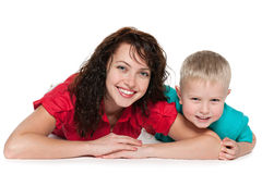 Happy mother with her son lie on the floor. On the white background Stock Photo