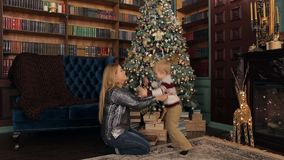 Happy mother and son playing near Christmas tree. stock footage