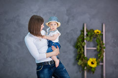A happy mother and her young daughter are having fun. They are both laughing. They are having casual clothes and floral wreathes o. N. The atmosphere of Royalty Free Stock Photography