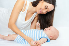Happy mother holding a baby boy at white background Stock Photography
