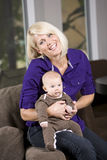 Happy mother holding baby on couch at home Stock Image