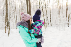 Happy mother holding baby girl on the walk in winter snowy forest royalty free stock photography
