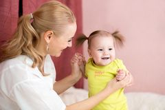 Happy mother holding baby hands Stock Images