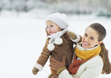 Happy mother holding baby looking on copy space in winter park Stock Photos