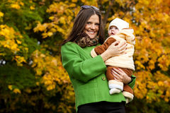 Happy mother holding baby in park Stock Images