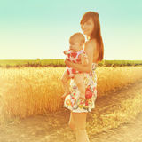 Happy mother holding baby smiling on a wheat field in sunlight. Outdoor shot. Portrait of mom and baby. Royalty Free Stock Photos