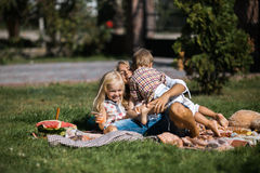 Happy mother holding both of her childrens. Mother with kids have fun on the grass stock photos