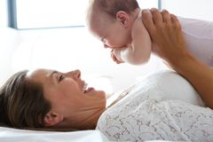Happy mother holding cute baby in bed Royalty Free Stock Photography