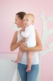 Happy mother holding cute baby in bedroom. Portrait of a happy mother holding cute baby in bedroom Stock Images