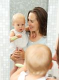 Happy mother holding cute baby with toothbrush Stock Photo