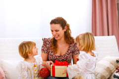Happy mother holding gift of her twins daughters Stock Photos