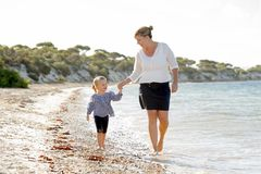 Happy mother holding hand of sweet blond little daughter walking together on sand at beach sea shore stock photo