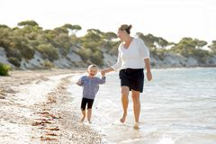 Happy mother holding hand of sweet blond little daughter walking together on sand at beach sea shore Royalty Free Stock Photography