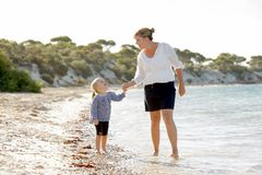 Happy mother holding hand of sweet blond little daughter walking together on sand at beach sea shore Stock Image