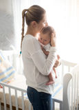 Happy mother holding her baby at bedroom. Portrait of happy mother holding her baby at bedroom Stock Photos