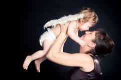 Happy mother holding her baby daughter with angel wings. On black Stock Images