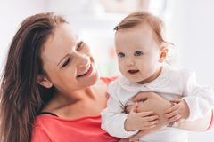 Happy mother holding her baby daughter. Looking at her. Motherhood concept Royalty Free Stock Photos