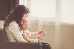 Happy mother holding her baby and playing with him indoors Stock Photo