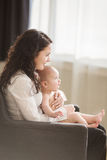 Happy mother holding her baby and playing with him indoors Stock Images