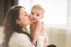 Happy mother holding her baby and playing with him indoors. Young mother kissing her little newborn baby Stock Image