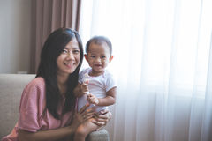 Happy mother holding her baby Stock Image