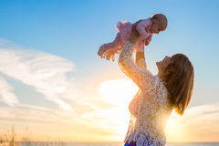 Happy mother holding her cute baby at sunset Stock Images