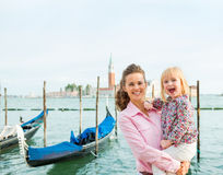 A happy mother holding her daughter in her arms in Venice Stock Image