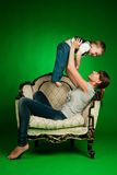 Happy mother holding her little boy up Stock Photos