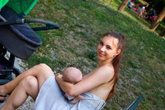 Happy smile mother holding little baby in her loving arms and breastfeeding outside in public stock images