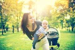 Happy mother holding and playing with newborn son. Happy woman holding infant, little kid and child Royalty Free Stock Images