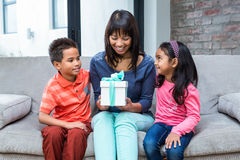 Happy mother holding a present and sitting with her children Royalty Free Stock Photo