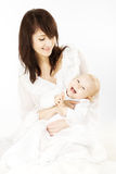 Happy mother holding smiling baby over white. Happy mother holding smiling playful baby over white Stock Images