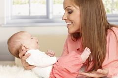 Happy mother holding tiny baby Stock Photography