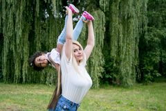 Happy mother holds her daughter. Happy mother playing with daughter at park stock photos