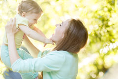 Happy mother holds little girl in park Royalty Free Stock Photos
