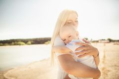 Happy mother huges baby. Mother holds child in her arms, baby hugging mom, close-up stock photography