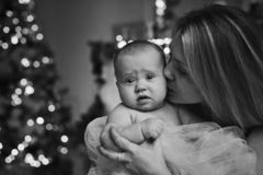Happy mother hugging baby daughter for the Christmas tree lights in the background royalty free stock photography