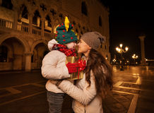 Happy mother hugging child with Christmas gift box in Venice Stock Photos