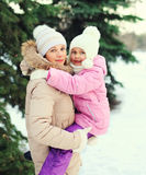 Happy mother hugging child near christmas tree in winter Stock Images