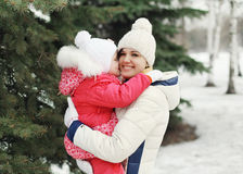 Happy mother hugging child near christmas tree in winter day Stock Photo