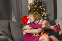 Happy mother hugging girl during Christmas at home Stock Photo