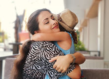 Happy mother hugging her daughter with love and natural emotion Stock Photography