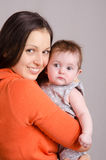 Happy mother hugging her daughter. Portrait of mother and baby at the hands of six mothers stock photography