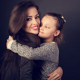 Happy mother hugging her fun daughter on dark grey background in Royalty Free Stock Photo