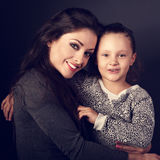 Happy mother hugging her fun daughter on dark grey background in Stock Photos