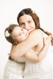 Happy Mother hugging her little pretty girl on white background. Royalty Free Stock Photography