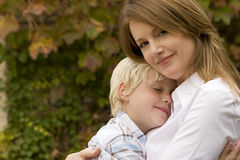 Happy mother hugging her son outside. Happy mother hugging her son outside at the park stock images